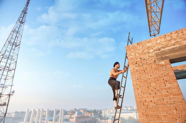 Vista laterale del costruttore bello con il torso nudo in cappello salire la scala. scala appoggiata su un muro di mattoni in un edificio finito. alta torre televisiva e paesaggio urbano sullo sfondo.