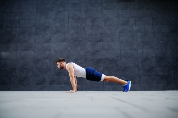 Side view of handsome caucasian muscular bearded man in shorts and t-shirt doing push-ups. in background is gray wall.