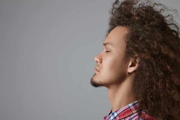 Vista laterale dell'uomo con la barba lunga di razza mista giovane concentrato bello con capelli ondulati voluminosi chiudendo gli occhi