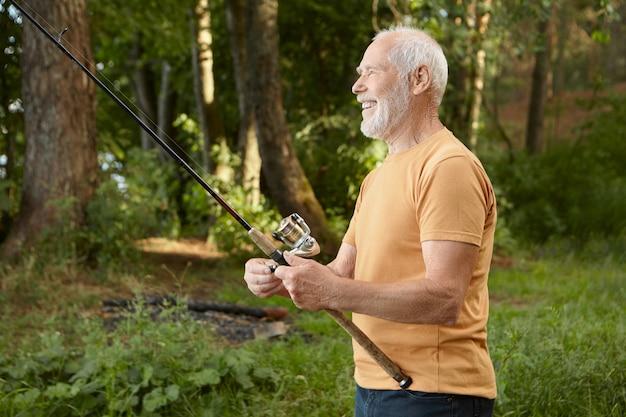 Vista laterale del pensionato maschio europeo bello che cattura pesci contro gli alberi di pino, tirando l'asta con cattura fuori dall'acqua, sorridendo felicemente, godendo di hobby all'aperto attivo nella natura selvaggia