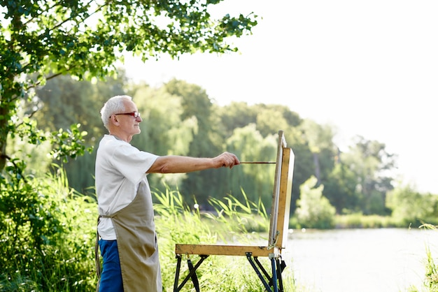Side view of handsome male painter drawing picture at daytime at park against lake.