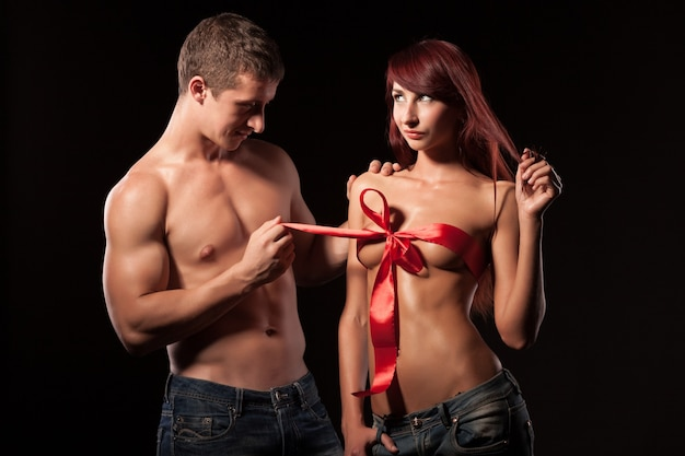 Side view of handsome man looking at naked girlfriend and pulling ribbon on lady breast.