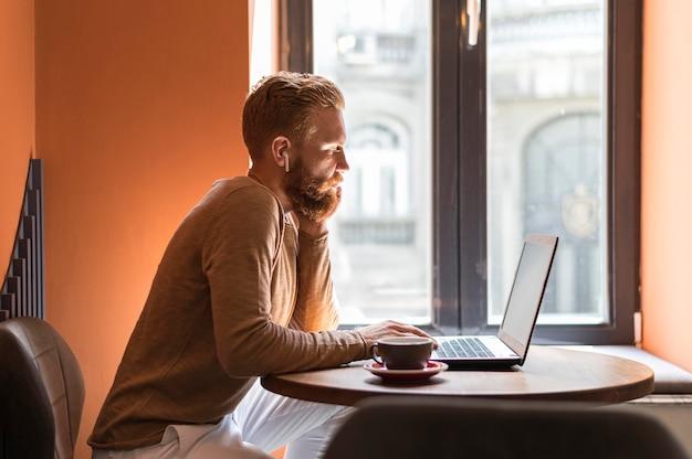 Uomo moderno bello di vista laterale che lavora