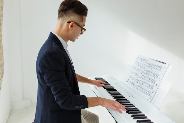 Side view of a handsome young man playing the piano