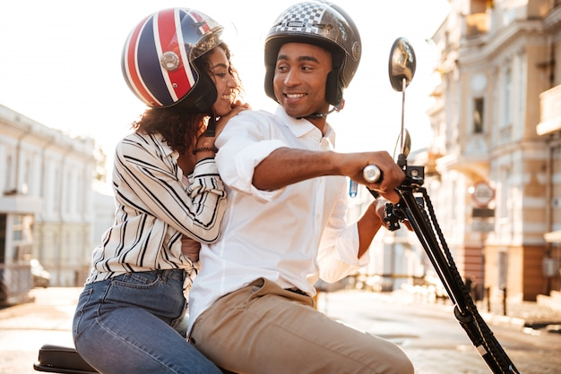 Side view of happy african couple rides on modern motorbike on the street