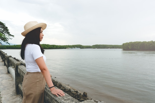 Side view of happy asian woman in hat standing and looking at river in evening sunset.