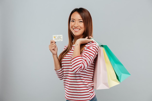 Side view of happy asian woman in sweater holding credit card and purchase while looking at the camera over gray background