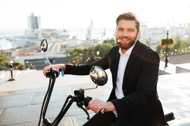 Vista laterale di felice uomo d'affari barbuto seduto sulla moto