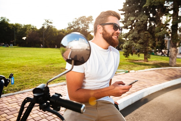 Side view of happy bearded man in sunglasses sitting on modern motorbike outdoors with smartphone and looking away