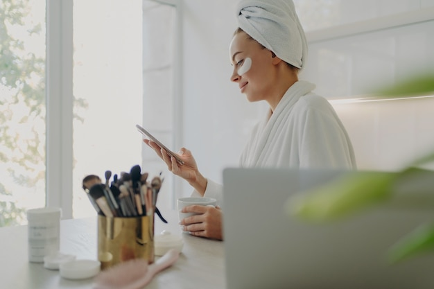 Side view of happy beautiful business woman in bathrobe with hair wrapped in towel and cosmetic patches under eyes using smartphone while getting ready for work in morning at home, standing in kitchen
