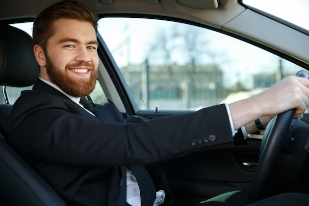 Side view of happy business man sitting at the wheel