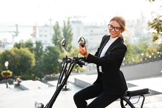 Vista laterale della donna felice di affari che si siede sulla motocicletta moderna