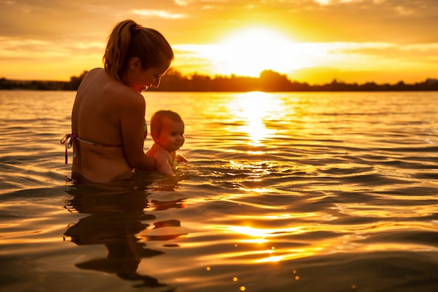 Side view of happy caucasian mother swimming with little cute smiling baby in sea