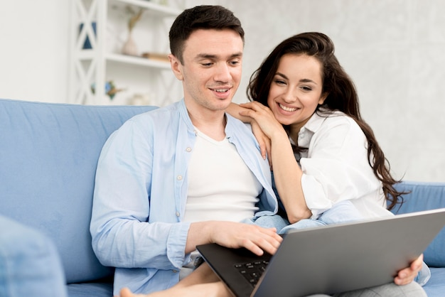 Side view of happy couple at home with laptop
