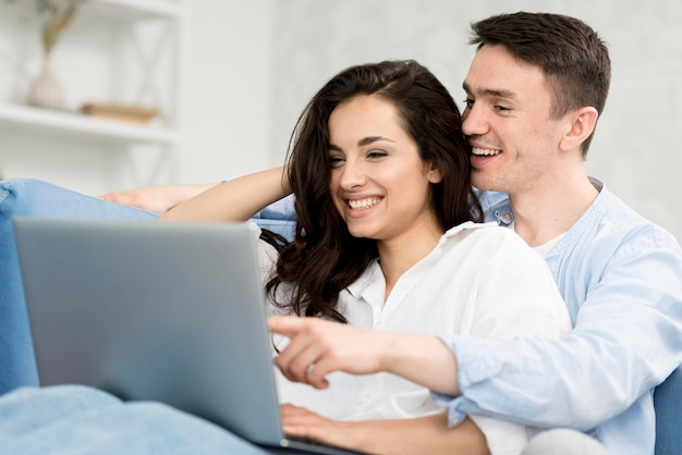 Side view of happy couple on sofa looking at laptop
