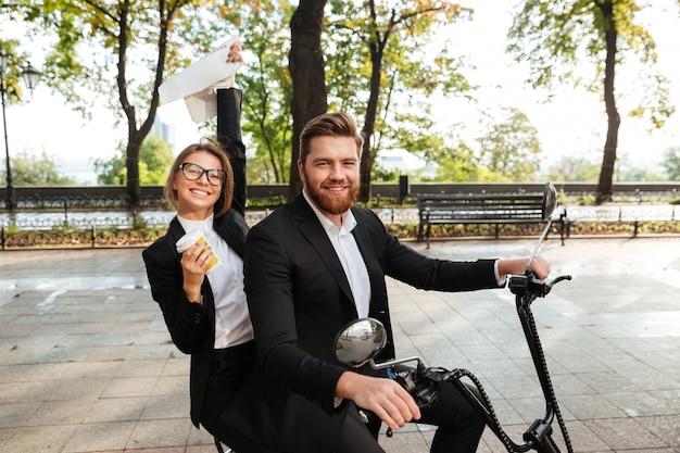Side view of happy elegant couple rides on modern motorbike