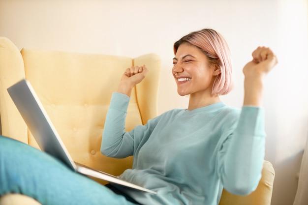 Vista laterale del libero professionista felice giovane donna emotiva in abiti casual seduto in poltrona con il computer portatile in grembo, stringendo i pugni, essendo eccitato per la grande offerta di lavoro, esclamando