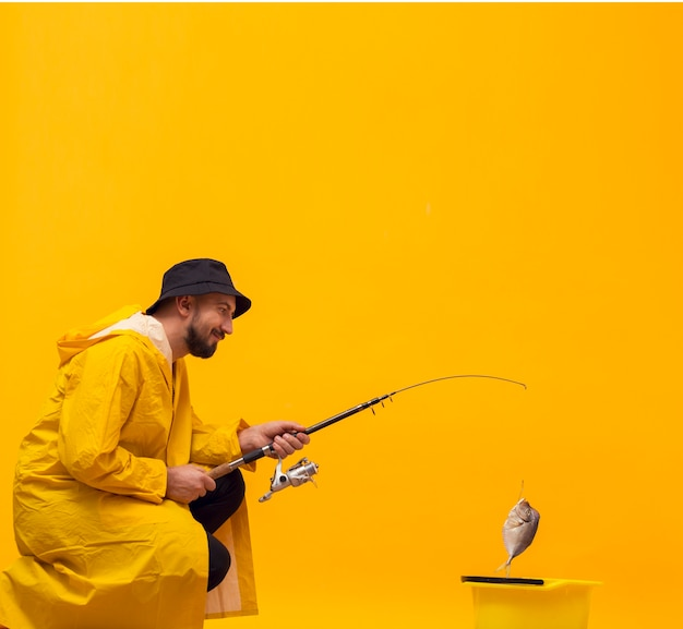Side view of happy fisherman holding fishing rod with catch
