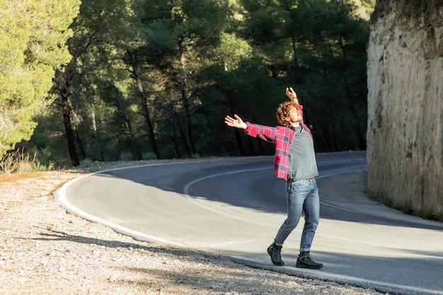 Vista laterale dell'uomo felice per godersi la natura durante un viaggio su strada