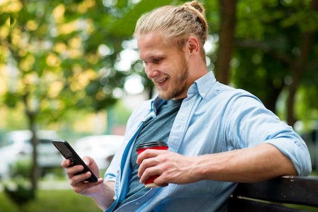 Vista laterale dell'uomo felice all'aperto con lo smartphone e la tazza