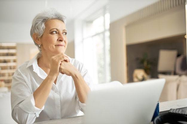 Side view of happy middle aged businesswoman with short gray hair working on laptop in her stylish office with hands on keyboard, typing letter, sharing good news