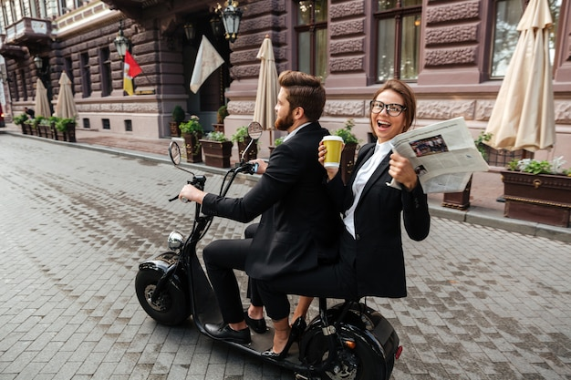 Side view of happy stylish couple rides on modern motorbike