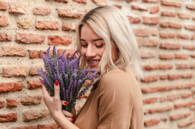 Side view of happy woman holding bouquet of lavender