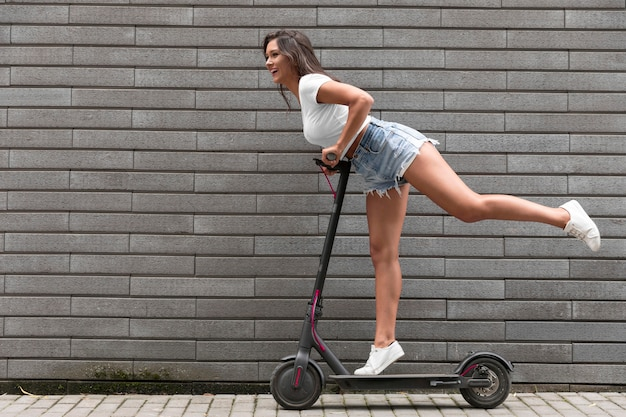 Side view of happy woman posing on electric scooter