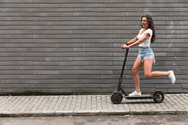 Side view of happy woman riding an electric scooter