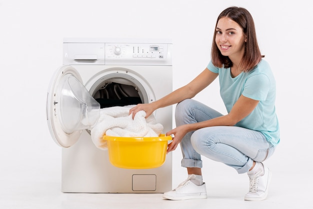 Side view happy woman taking towels from washing machine