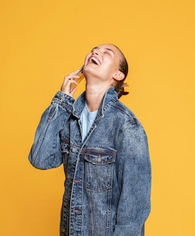 Vista laterale della donna felice che parla sullo smartphone