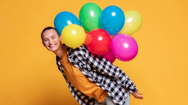 Side view of happy woman with multicolored balloons