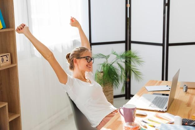 Vista laterale della donna felice che lavora a casa