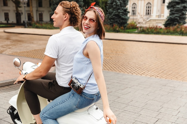 Side view of happy young lovely couple riding together on scooter outdoors