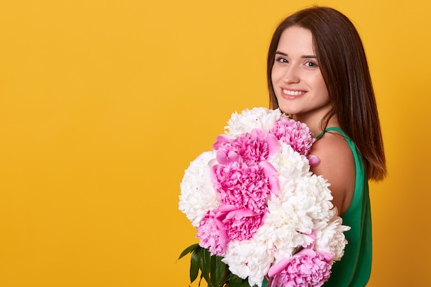 Side view of happy young woman wearing green attire, holding white and pink peonies in hands