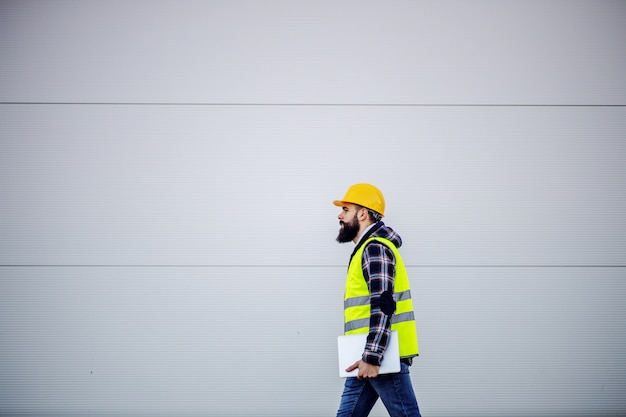 Side view of hardworking construction worker with safety helmet on head and in vest holding laptop in hands and rushing on construction site.