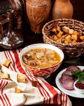 Side view hash traditional azerbaijani dish in a kyasa plate with onions and crackers