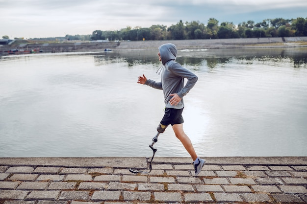Side view of healthy caucasian handicapped sportsman in sportswear and with artificial leg running on quay.