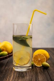 Vista laterale di un sano succo di limone in un bicchiere con limoni e kinkan su un vassoio di vimini su un tavolo di legno su una superficie bianca