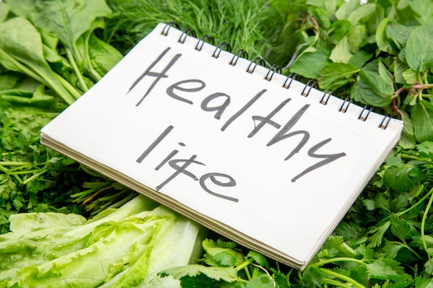 Side view of healthy life inscription on spiral notebook on bundles of fresh greens on white table