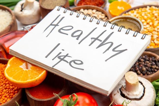 Vista laterale di un'iscrizione di vita sana su quaderno a spirale su verdure fresche chicchi di mais limone limone bottiglia di olio caduta miele su sfondo bianco