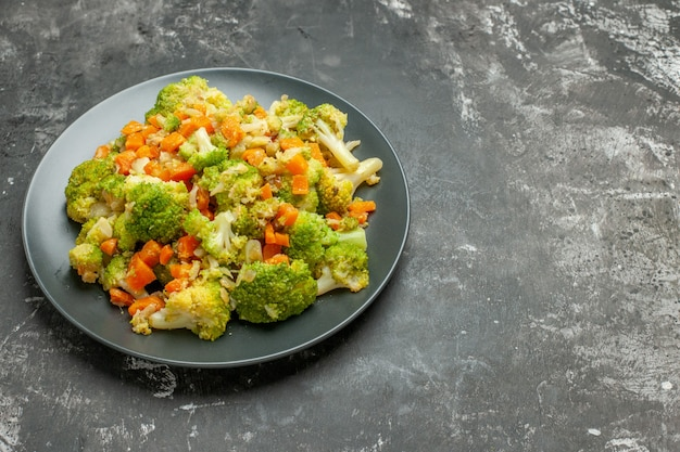 Vista laterale del pasto sano con broccoli e carote su un piatto nero e sul tavolo grigio