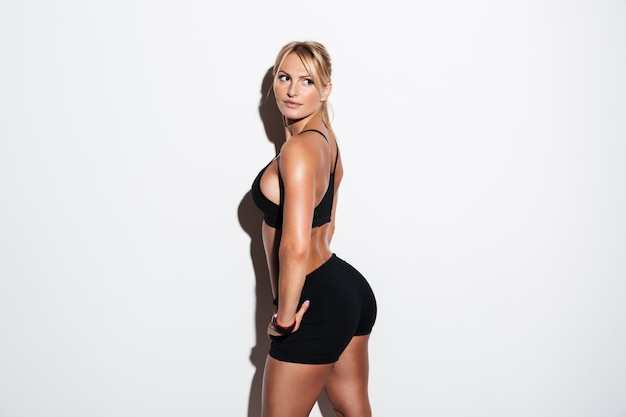 Side view of a healthy sportswoman posing and looking away