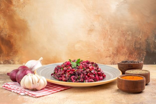 Vista laterale sana insalata di verdure su un piatto con verdure fresche su con pepe nero curcuma pepe nero macinato a destra e cipolle rosse aglio a sinistra su sfondo chiaro con copia posto
