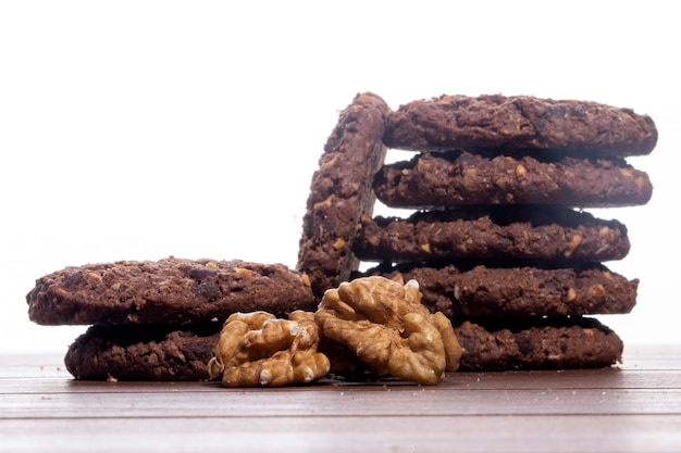 Side view of a heap of chocolate chip cookies with cereals nuts and cocoa on the table