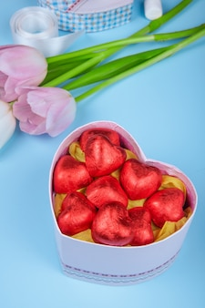 Side view of heart shaped chocolate candies wrapped in red foil in a heart shaped gift box and pink color tulips on blue table