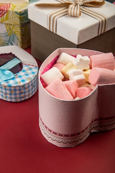 Side view of a heart shaped present box filled with marshmallow on red table