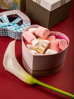 Side view of heart shaped present box filled with marshmallow and white calla lily on red table