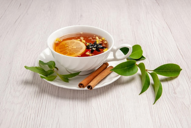 Side view herbal tea a cup of herbal tea with lemon and cinnamon sticks on the saucer and leaves on the white table