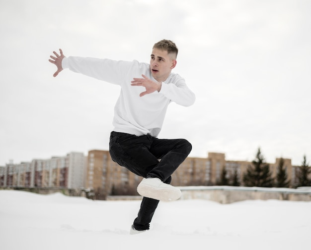 Vista laterale dell'artista hip-hop che posa mentre ballando